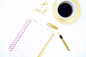 gold pen, notebook and coffee cup and saucer
