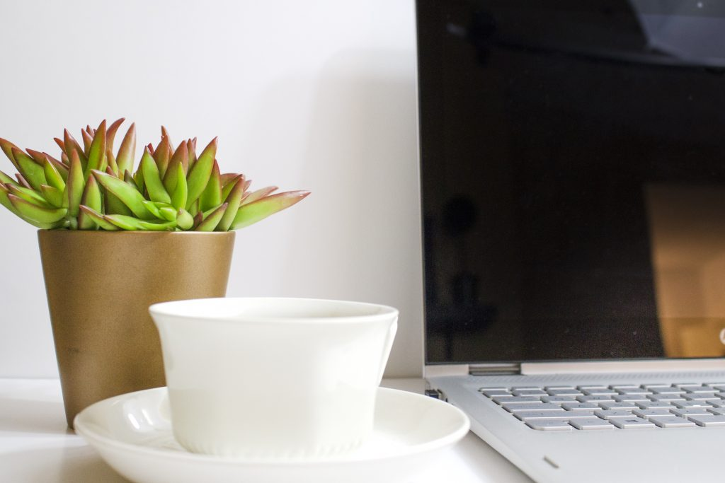 simple desk with laptop coffee and plant pot