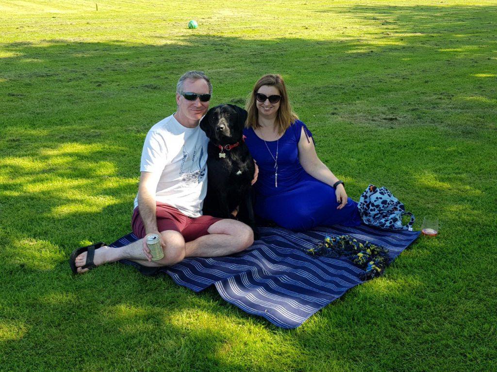a couple with their black Labrador