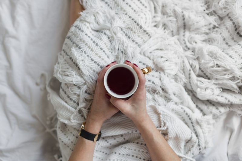 Soft photo of woman on the bed with the book and cup of tea in hands
