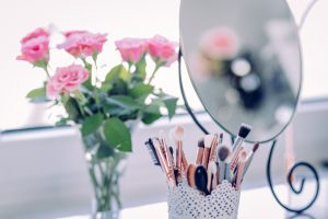 dressing table with flowers and make up brushes