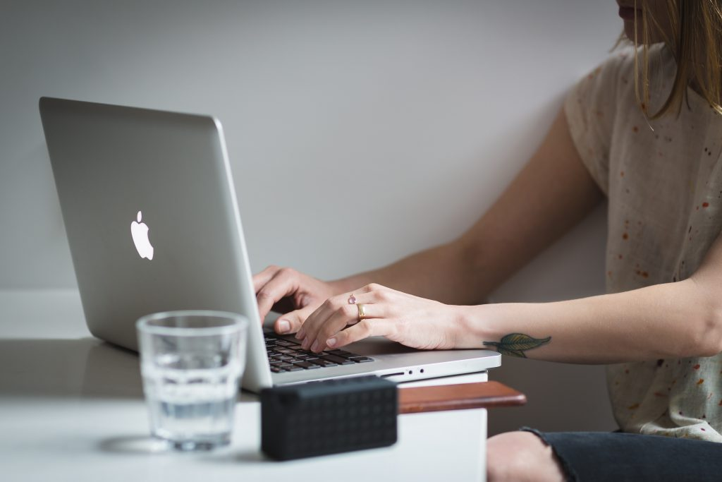 woman working on laptop with a glass of water
